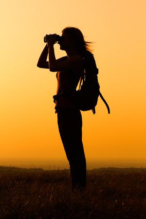 双眼鏡で夕日を見て女性ハイカーのシルエット。