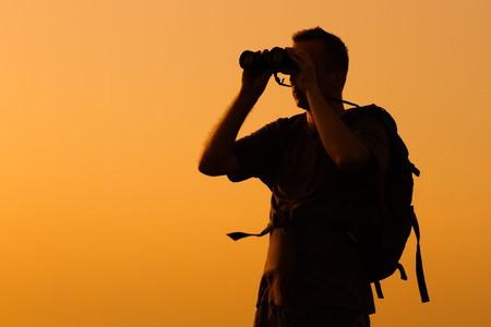 Silhouette of man watching sunset with binoculars .