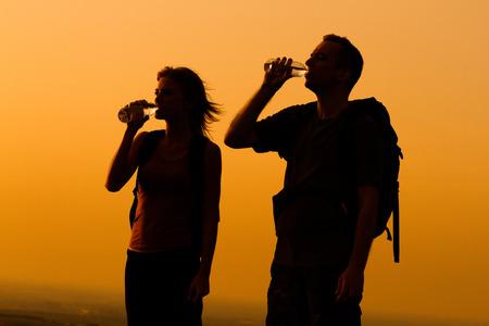 tomando agua: Silueta de una mujer y el hombre con el agua potable mochila.