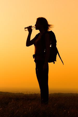 tomando agua: Silueta de una mujer con el agua potable mochila.