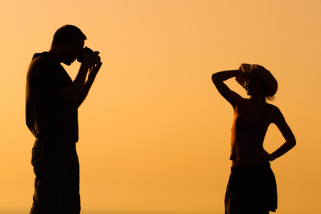 Silhouette of a man photographing woman outdoor.