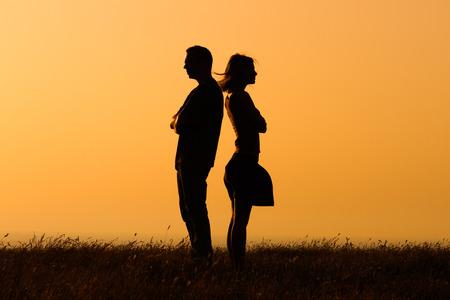 marido y mujer: Silueta de una mujer enojada y el hombre en la otra. Foto de archivo