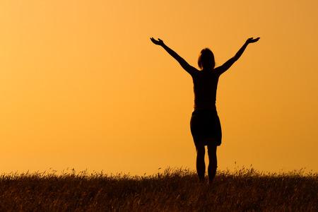 幸せな女性は、日没で楽しんでいます。