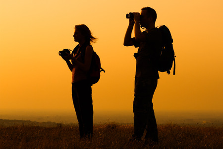heterosexual couple: A silhouette of a woman and man with backpack looking at sunset.