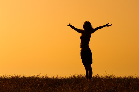 Happy woman enjoys in sunset. Banque d'images