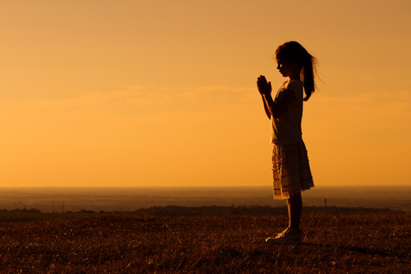 Silhouette of a cute little girl meditating.