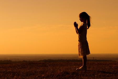 ni�o orando: Silueta de un poco de meditaci�n linda chica. Foto de archivo