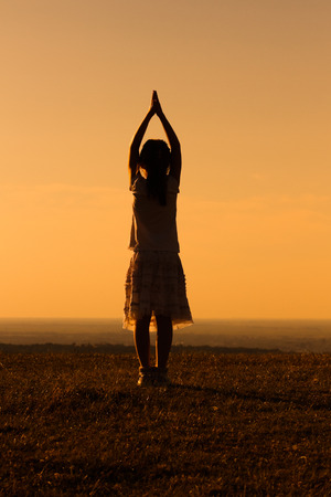 unrecognizable: Silhouette of a little girl meditating.