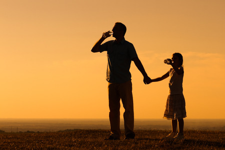 Father and daughter are drinking water at sunset. Stock Photo