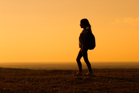 unrecognizable: Cute little hiker girl looking at sunset.