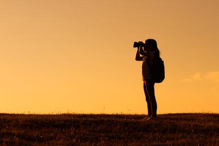 日没を双眼鏡で見てかわいいの少しのハイカーの女の子。 写真素材