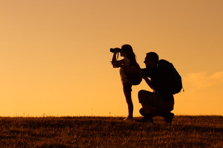 curious: Silhouette of father and daughter hiking together.