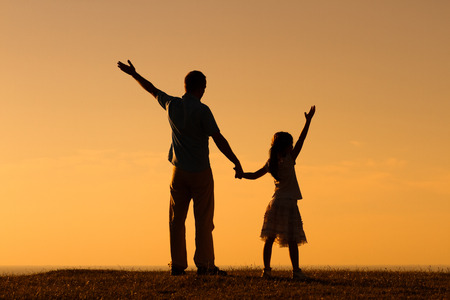 family praying: Father and daughter enjoy in sunset together.