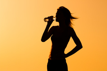standing water: A silhouette of a woman drinking water.
