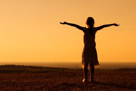 幸せな少女は、日没で楽しんでいます。 写真素材