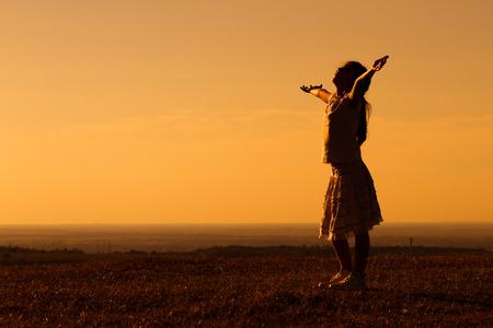 ni�o orando: Ni�a feliz disfruta de la puesta del sol.