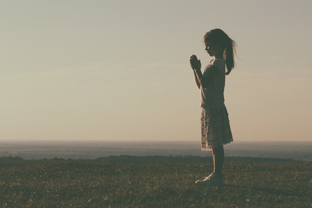 Silhouette of a cute little girl meditating.Image is intentionally with grain and toned. Stock Photo