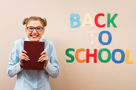 holding back: Happy geek girl  is excited because she is going back to school. Stock Photo