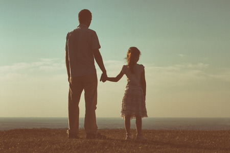day care: Father and daughter enjoy watching sunset together.Image is intentionally with grain and toned.