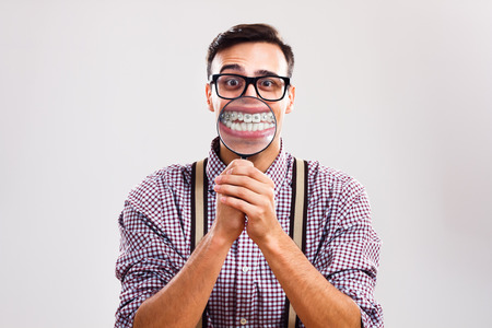 magnifying glass man: Nerdy man is holding loupe and showing his teeth with braces. Stock Photo
