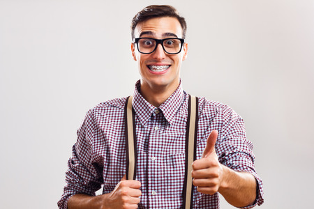 Happy nerdy man is showing thumb up.