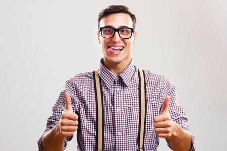 sticking out tongue: Happy nerdy man sticking out tongue and  showing thumb up. Stock Photo