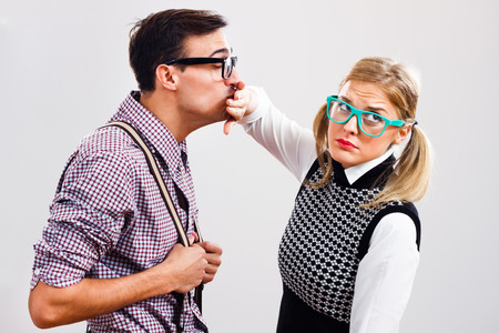 Nerdy man is trying to kiss his nerdy lady ,but she is pushing him away.