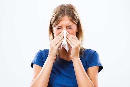 gripa: La mujer está estornudando en un pañuelo.