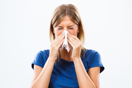 holding nose: Woman is sneezing into handkerchief. Stock Photo