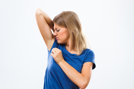 Young woman is sweating to much and she doesn't like her smell under armpit. Stockfoto