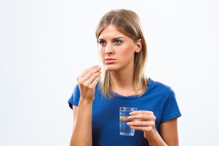 pastillas: Retrato de mujer joven tomando pastillas. Foto de archivo