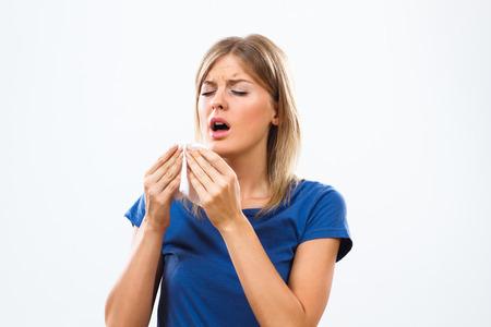 De jonge vrouw heeft griep en ze is niezen.