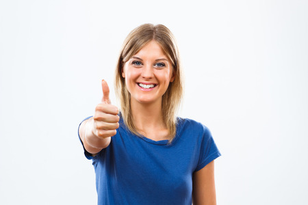 woman thumbs up: Portrait of young woman showing thumbs up.