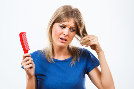 loosing: Young woman is in panic because she is loosing her hair. Stock Photo