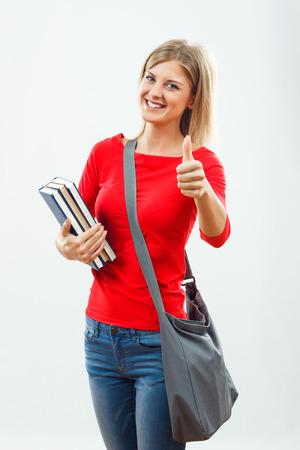 Ritratto di bella studentessa che mostra i pollici in su femminili.