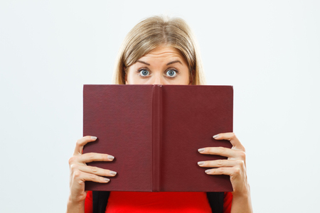 Blue eyed female student is hiding behind a book.