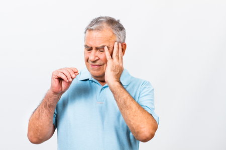 headache: Senior man is having headache and he is about to take some pills to help himself.