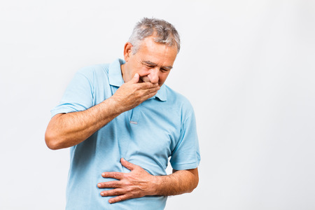 Senior man doesn't feel good and he is going to vomit. Stock Photo