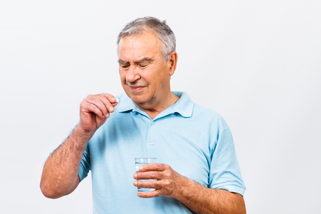 one mature man only: Portrait of senior man taking pills. Stock Photo