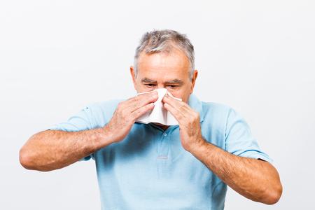 flu shots: Senior man is sneezing into handkerchief. Stock Photo