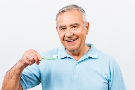 dental health: Portrait of senior man holding toothbrush. Stock Photo