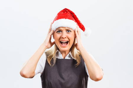 emotional stress: Business woman with Santa Hat is in panic because eof something.