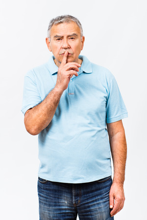 Portrait of a senior man with finger on his lips. Stock Photo