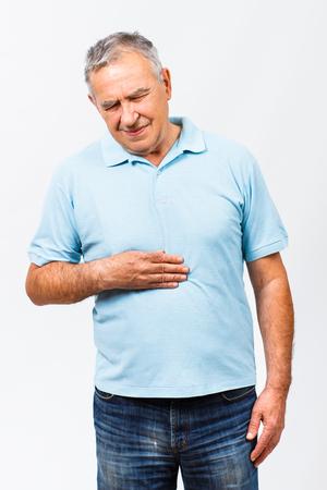Lterer Mann ist mit Schmerzen im Magen. Standard-Bild - 47041657