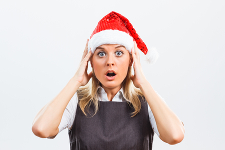 shocked: Business woman with Santa Hat is shocked and in panic because of something.