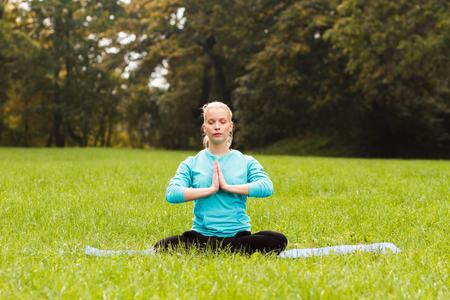 buena postura: Joven practicando yoga en el parque. Foto de archivo