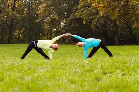 good posture: Amigos practicando yoga juntos en el parque. Foto de archivo
