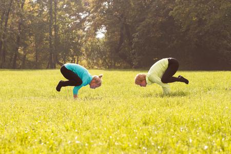 buena postura: Amigos practicando yoga juntos en el parque. Foto de archivo