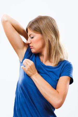 mujer fea: Mujer joven está sudando mucho y que no le gusta su olor debajo de la axila.