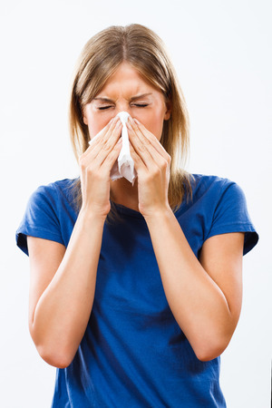 Woman is sneezing into handkerchief. Stock Photo